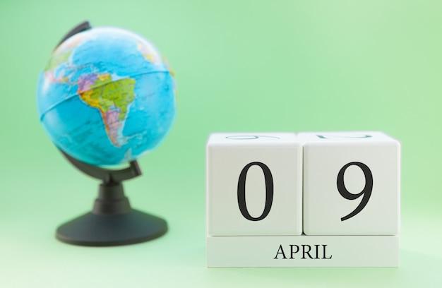 Frühling 9. april kalender. teil eines sets auf unscharfem grünem hintergrund und kugel.
