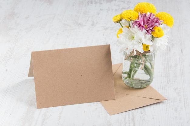 Frühling blüht blumenstrauß in einem glasvase mit kartenanmerkung und umschlag auf einem weißen hölzernen rustikalen hintergrund