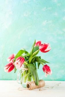 Frühling . blüht tulpen in einem glasweinglas, auf einem hellblauen und hölzernen weiß.