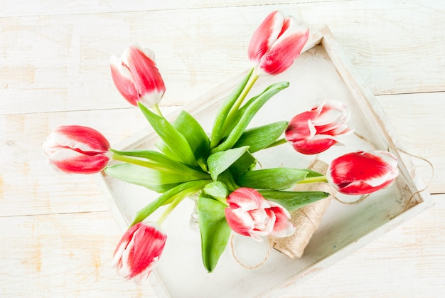 Frühling . blüht tulpen in einem glasweinglas, auf hölzernem weiß. ansicht von oben
