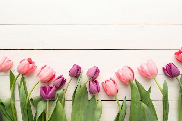 Frühling, blumenkonzept. rosa und lila tulpen über weißem holztischhintergrund