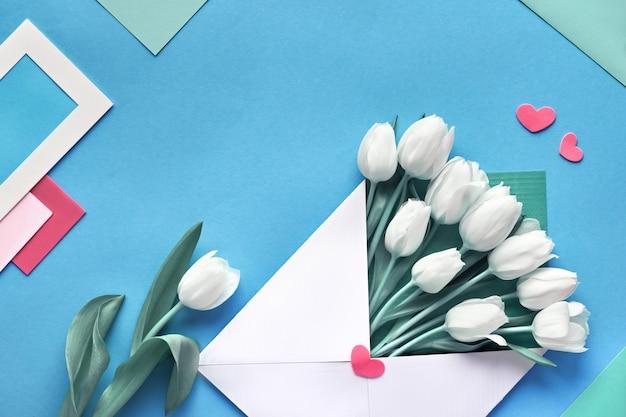 Frühling flach lag, weiße tulpen im papierumschlag auf blauem minzhintergrund mit umschlägen, karten und herzen