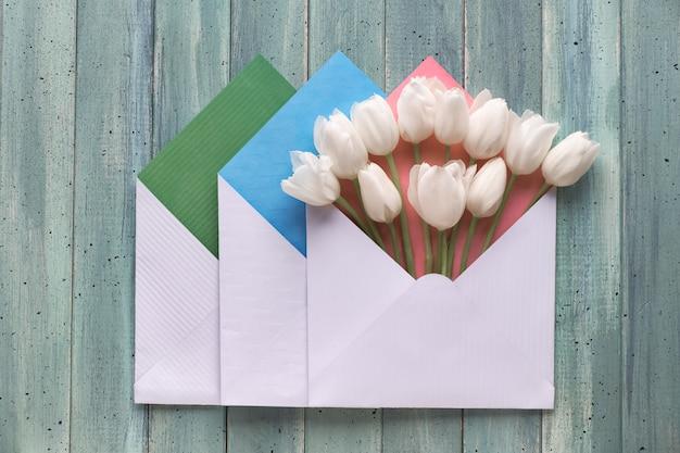 Frühling flach legen, drei papierumschläge mit weißen tulpen