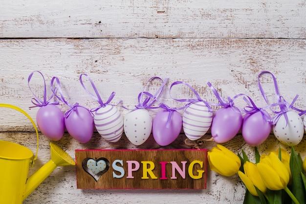 Frühling hintergrund mit blumen und ostereier in der reihe