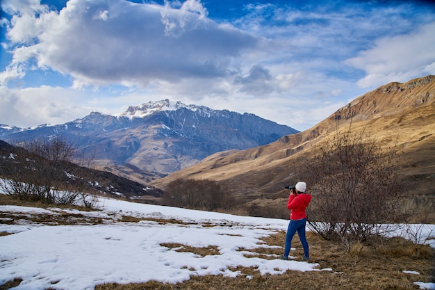 Frühling in den bergen, der schnee schmolz. das mädchen fotografiert die landschaft.