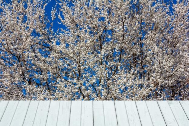 Frühling mit blühenden bäumen und weißen holzbrettern für die produktausstellung