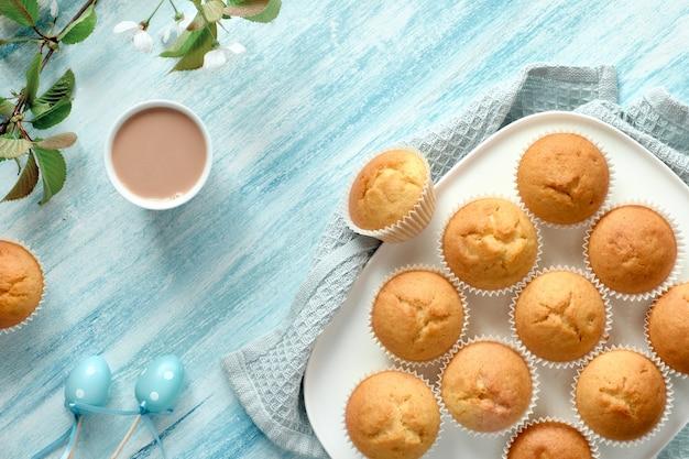 Frühling oder ostern flach legen mit teller mit zitronen-muffins und marzipan-eiern