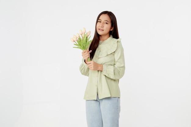 Frühling schönes fröhliches mädchen, das lächelt und einen strauß tulpenblumen hält. junge glückliche asiatische frau.