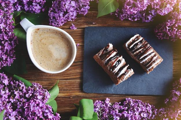 Frühling und frisches frühstück auf einem holztisch. auf dem tisch liegen flieder, kuchen und ein cappuccino. ein blumenstrauß aus flieder auf einem holztisch.