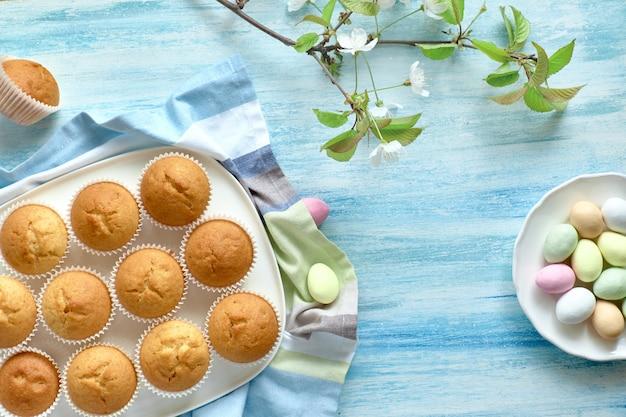 Frühlings- oder osterwohnung lag mit teller mit zitronenmuffins und marzipaneiern auf hellblauem hintergrund mit frischen apfelblumen