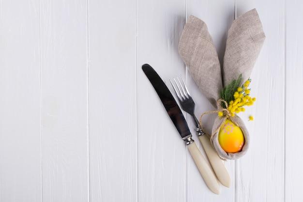 Frühlings-osterhintergrund für menü. osterei dekoration, hasenohren leinenserviette und küchenbesteck auf weißem holztisch