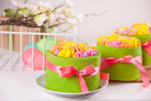Frühlings ostern festlichen tisch. kleine grüne kuchen mit buttercremeblumen und bunten eiern.