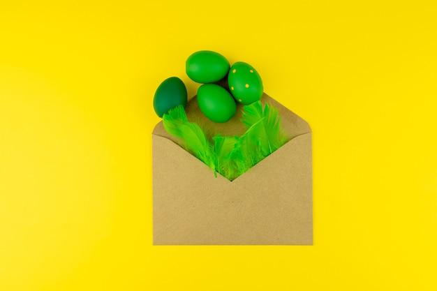 Frühlings-ostern-layout mit grünen federn und eiern, bastelumschlag auf gelbem hintergrund. kopieren sie platz für text für text.