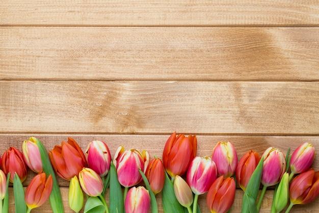 Frühlings-ostertulpen im eimer auf hölzernem weinlesehintergrund.