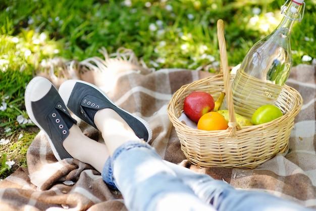 Frühlings-picknick-konzept. picknickkorb mit früchten, blumen und wasser in der glasflasche