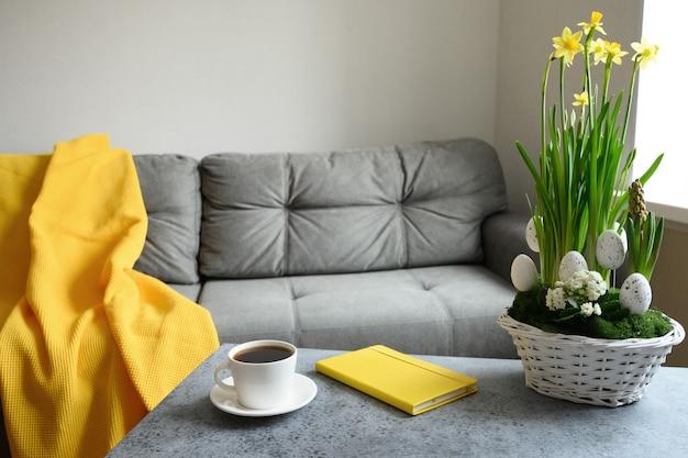 Frühlings- und osterblumenzusammensetzung in blumentopf und kaffee auf dem tisch im wohnzimmer mit grauer couch und gelbem pled. frühlingswochenende planen.