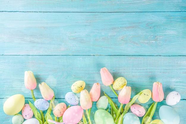Frühlings- und osterferienhintergrund mit tulpenblumen, bunte pastelleier auf blauer tischoberansicht. frohe ostern-grußkarte.