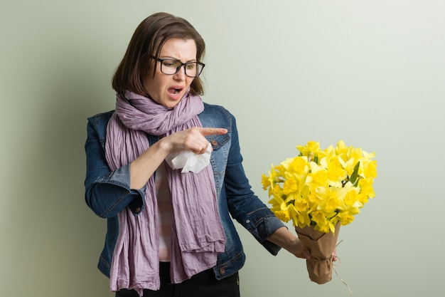 Frühlingsallergie gegen pollen. frau mit gelbem blumenstrauß wird niesen.