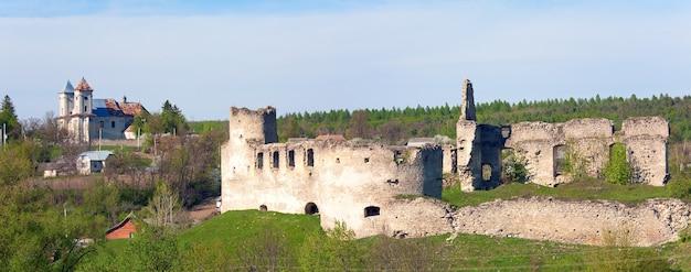 Frühlingsansicht der burgruine sydoriv (erbaut in den 1640er jahren) und der katolitsky-kirche (erbaut 1730-1741). dorf sydoriv, 7 km südlich von husiatyn, region ternopil, ukraine. stichbild mit zwei schüssen.