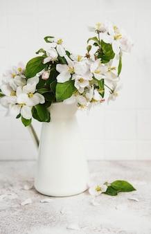 Frühlingsapfelblüte in einer weißen vase auf dem tisch