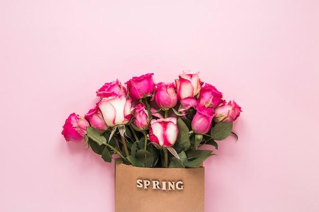 Frühlingsaufschrift in der papiertüte mit rosen