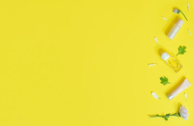Frühlingsbanner mit kosmetik und blumen auf einem gelben