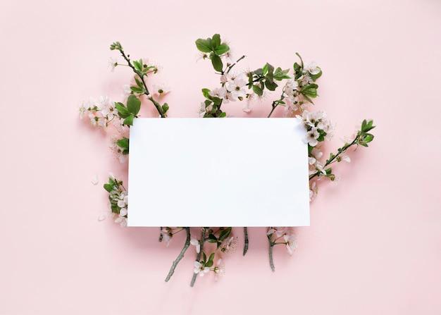 Frühlingsblüte und weiße leere karte auf pfirsichhintergrund mock-up-bild