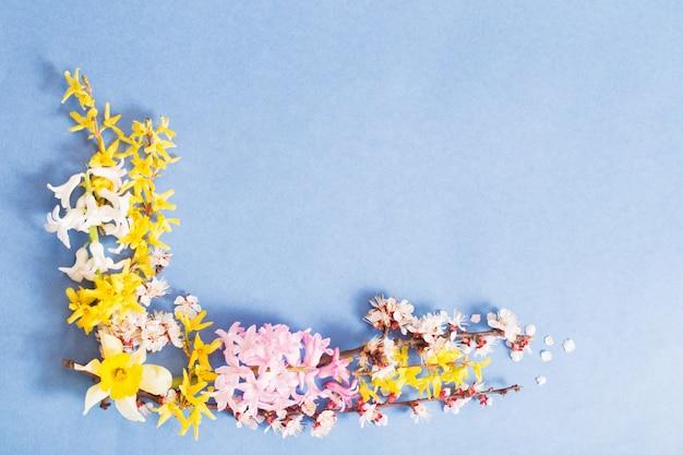 Frühlingsblumen auf blauem papierhintergrund