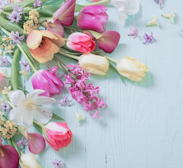 Frühlingsblumen auf blauer holzoberfläche