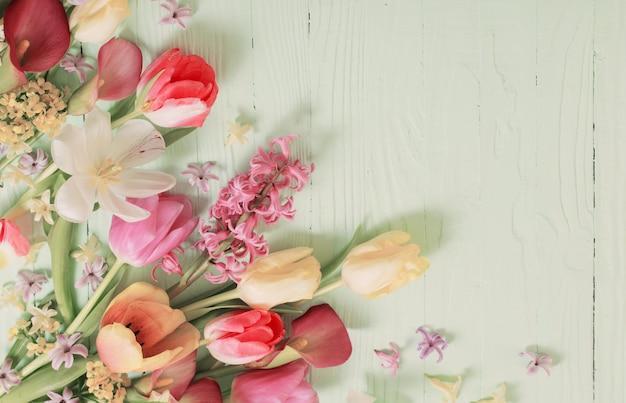 Frühlingsblumen auf grünem holzhintergrund