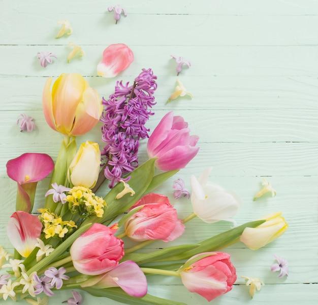 Frühlingsblumen auf grünem holzhintergrund Premium Fotos
