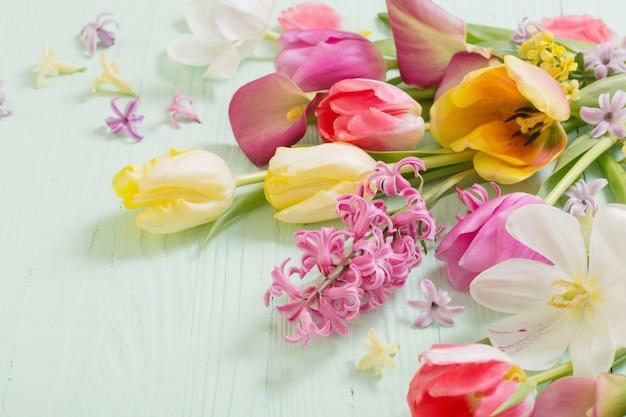 Frühlingsblumen auf grüner holzoberfläche