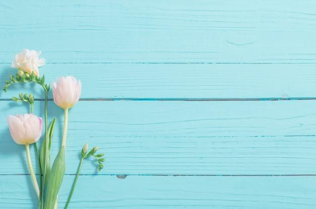 Frühlingsblumen auf hölzernem hintergrund der blauen minze