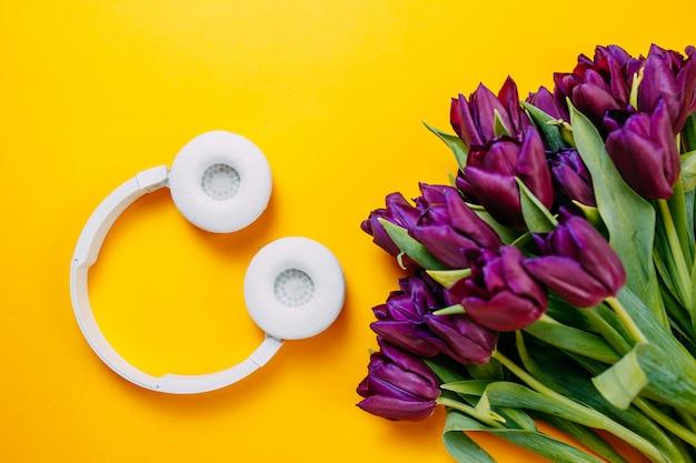 Frühlingsblumen, bündel lila tulpen auf orange hintergrund, weiße drahtlose kopfhörer auf orange hintergrund.