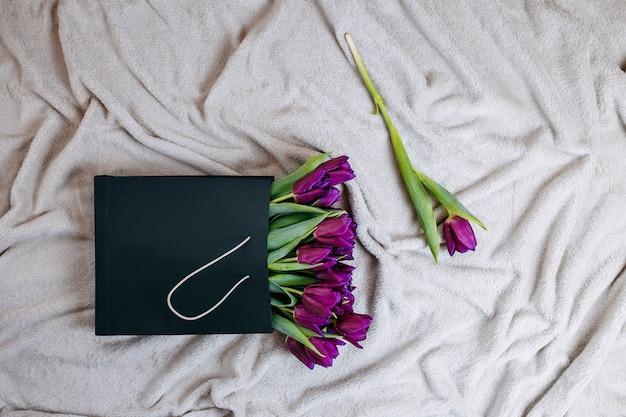 Frühlingsblumen, bündel lila tulpen in schwarzer papiertüte auf dem beigen plaid.