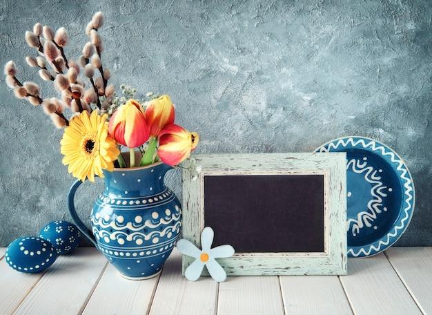 Frühlingsblumen im blauen keramikkrug mit passendem teller und ostereiern und einer tafel