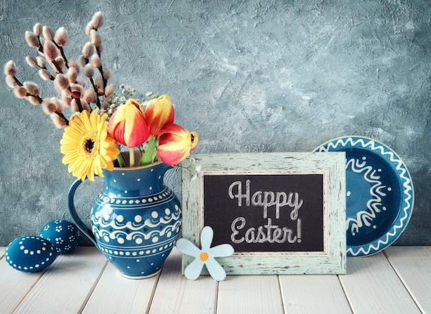 Frühlingsblumen im blauen keramikkrug mit passendem teller und ostereiern und einer tafel.