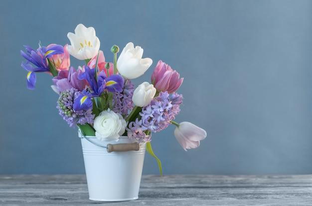 Frühlingsblumen im eimer auf blauem hintergrund