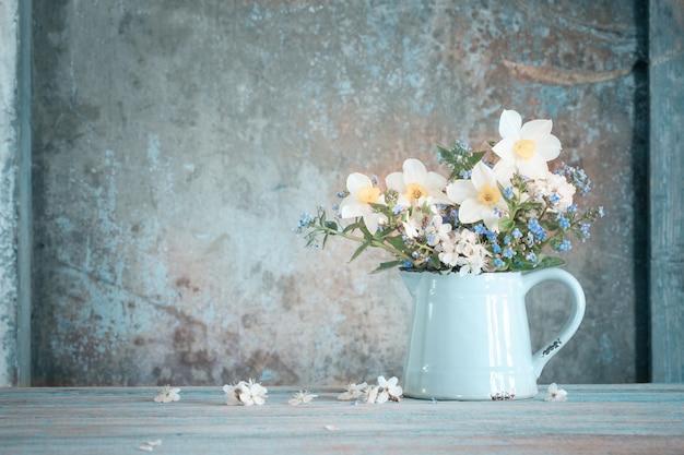 Frühlingsblumen im krug auf altem gemaltem hölzernem hintergrund