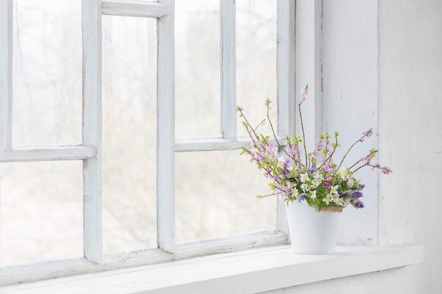 Frühlingsblumen im weißen eimer auf altem weißem fensterbrett