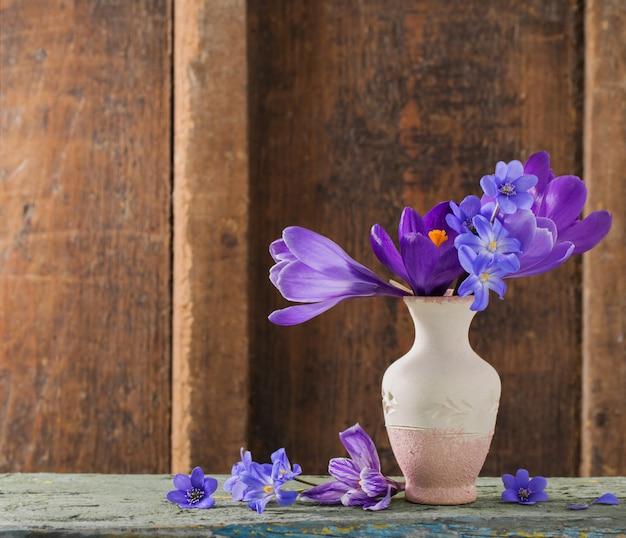 Frühlingsblumen in der vase auf hölzernem raum