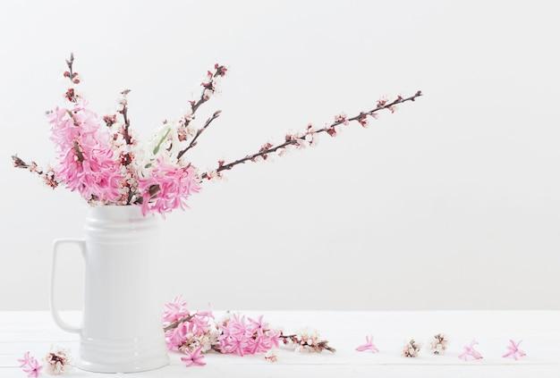Frühlingsblumen in der vase auf weißem hintergrund