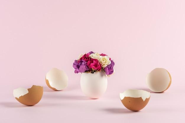 Frühlingsblumen in gebrochener eierschale mit zerbrochenen ostereiern auf pastellrosa hintergrund