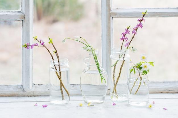 Frühlingsblumen in gläsern auf altem weißem fensterbrett