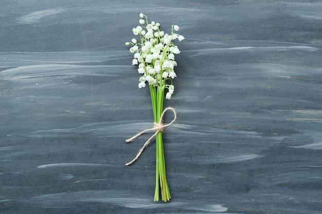 Frühlingsblumen maiglöckchen auf grauem vintage gemaltem hintergrund