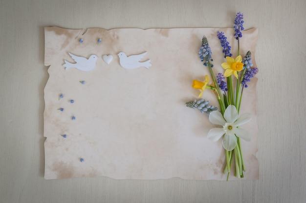 Frühlingsblumen mit papier für text und zwei hölzernen vögeln und herz. hochzeits-, verlobungs- oder verlobungskonzept auf einem hölzernen hintergrund. kopierraum, draufsicht. grußkarte. .