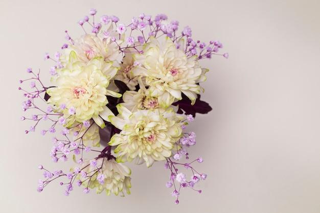 Frühlingsblumen, nahaufnahme von gelben, blassrosa chrysanthemen und kleinen lila blüten auf einer weichen, ruhigen leere