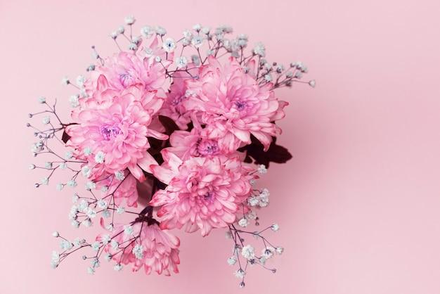 Frühlingsblumen, nahaufnahme von leuchtend rosa, blassrosa chrysanthemen und kleinen lila blüten, blumenstraußkomposition.