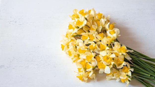 Frühlingsblumen narzissen auf einem holztisch.