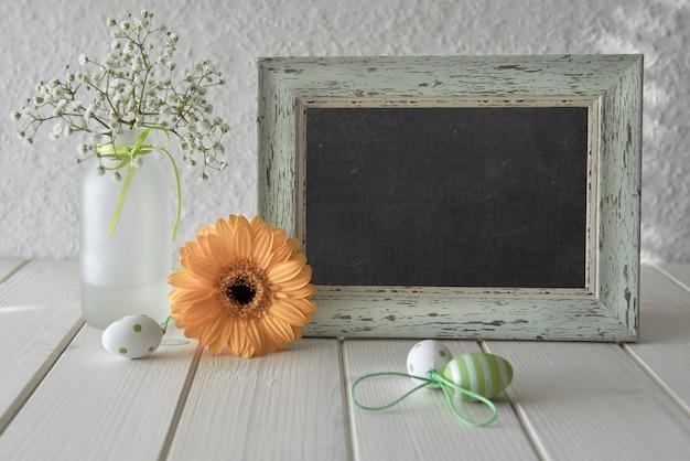 Frühlingsblumen, osterdekorationen und eine tafel auf weißem tisch